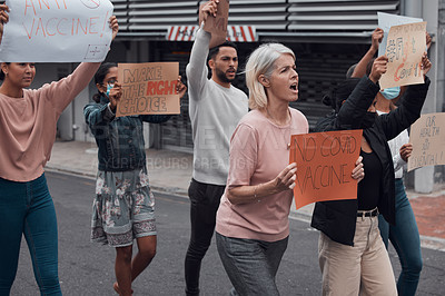 Buy stock photo Cropped shot of a group of demonstrators holding up signs protesting against the covid 19 vaccine