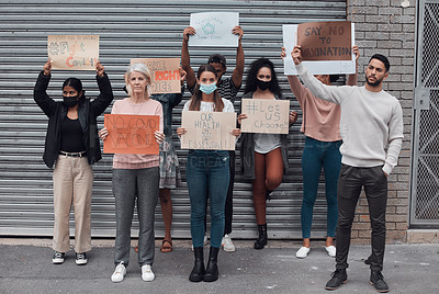 Buy stock photo Full length portrait of a group of demonstrators holding up signs protesting against the covid 19 vaccine