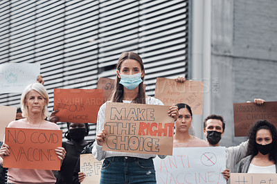 Buy stock photo Cropped portrait of an attractive young woman holding up a sign protesting against the covid 19 vaccine with other demonstrators in the background