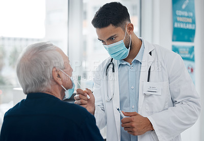 Buy stock photo Cropped shot of a handsome young male doctor testing a senior patient for covid