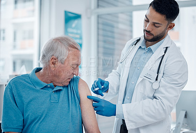 Buy stock photo Cropped shot of a handsome young male doctor administering the covid 19 vaccine to a senior patient