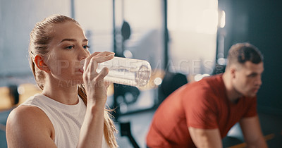 Buy stock photo Shot of a woman drinking a bottle of water during her workout at the gym