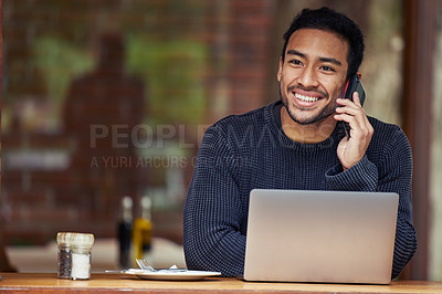 Buy stock photo Shot of a man talking on his cellphone and using his laptop while sitting in a cafe