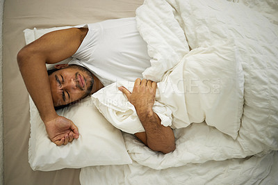 Buy stock photo Shot of a young man frowning while lying in his bed