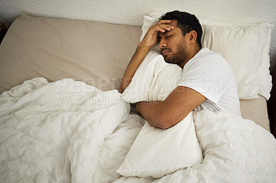 Buy stock photo Shot of a man cuddling a pillow while sleeping in his bed