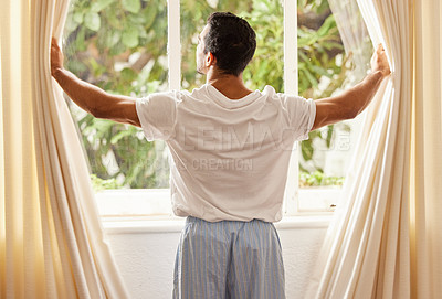 Buy stock photo Shot of a man opening the curtains at home on a sunny day