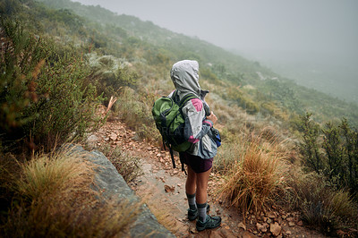 Buy stock photo Shot of a woman wearing her rain jacket while out hiking