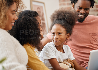 Buy stock photo Shot of a young family spending time together and using a digital tablet at home