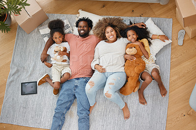 Buy stock photo Aerial shot of a young family lying on the floor at home