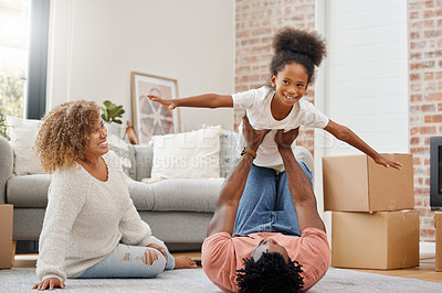 Buy stock photo Shot of a young dad holding his daughter up in the air with his arms and legs at home