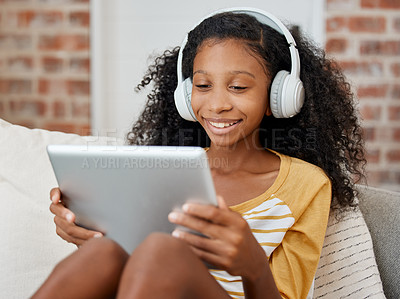 Buy stock photo Shot of a girl using a tablet while sitting on the couch at home