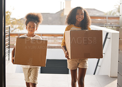 Buy stock photo Shot of two sisters carrying boxes into their new home