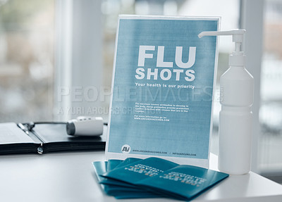 Buy stock photo Shot of a sign, pamphlets and hand sanitiser on a desk in an office
