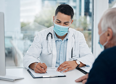 Buy stock photo Shot of a young doctor writing down information in an office