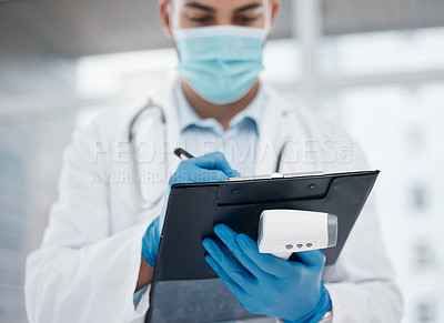 Buy stock photo Shot of a young doctor writing down information while holding a thermometer in an office
