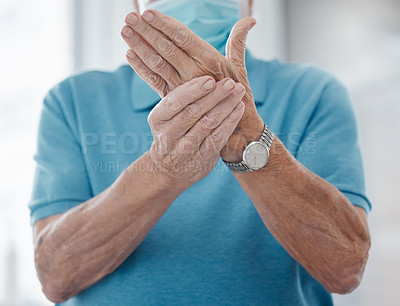Buy stock photo Shot of an unrecognizable man feeling his hands in a hospital