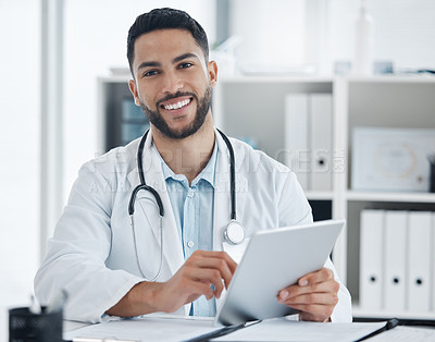 Buy stock photo Shot of a young doctor using a digital tablet in an office