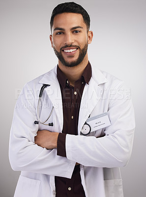 Buy stock photo Shot of a handsome young doctor standing alone in the studio with his arms folded