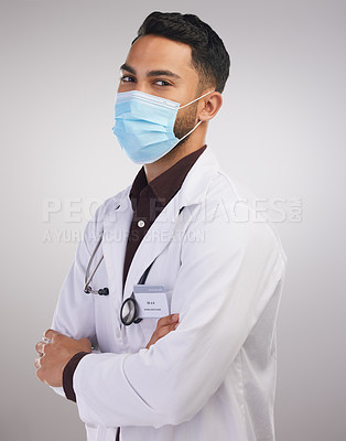 Buy stock photo Shot of a handsome young doctor standing alone in the studio with his arms folded and wearing a face mask