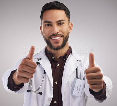 Buy stock photo Shot of a handsome young doctor standing alone in the studio and making a thumbs up hand gesture
