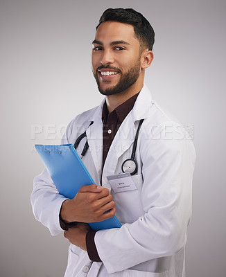 Buy stock photo Shot of a handsome young doctor standing alone in the studio and holding a clipboard