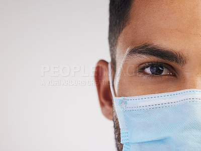 Buy stock photo Cropped shot of an unrecognizable nurse standing alone in the studio and wearing a face mask