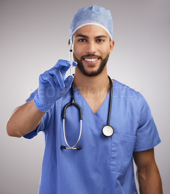 Buy stock photo Shot of a handsome young nurse standing alone in the studio and holding a syringe
