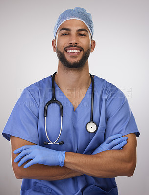 Buy stock photo Shot of a handsome young nurse standing alone in the studio with his arms folded
