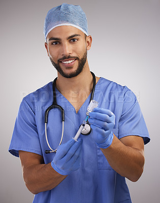 Buy stock photo Shot of a handsome young nurse standing alone and using a syringe to prepare a Covid vaccination
