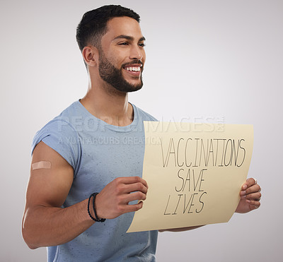 Buy stock photo Shot of a handsome young man sitting alone in the studio and holding a poster after getting vaccinated