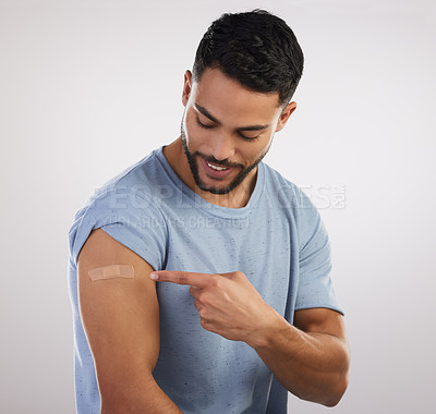 Buy stock photo Shot of a handsome young man sitting alone in the studio after getting vaccinated