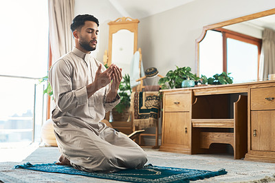 Buy stock photo Shot of a young muslim man praying in the lounge at home