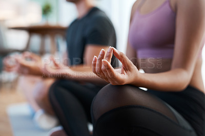 Buy stock photo Cropped shot of an unrecognizable and athletic young couple meditating during their workout at home