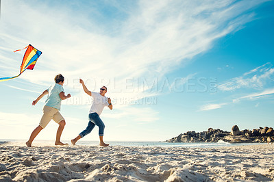 Buy stock photo Shot of a mature couple on the beach with a kite