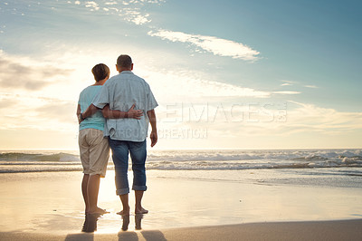 Buy stock photo Rearview shot of a couple admiring the view while at the beach