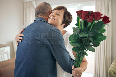 Buy stock photo Shot of a mature wife hugging her husband for the gift of roses