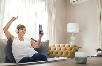 Buy stock photo Shot of a mature woman using her smartphone to take a selfie while listening to music