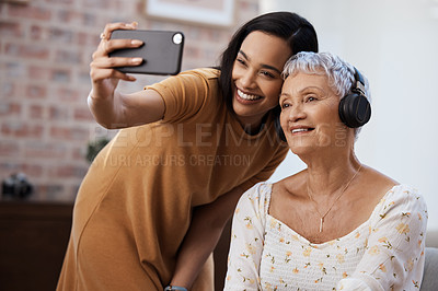 Buy stock photo Shot of a senior woman using a smartphone to take selfies with her daughter at home