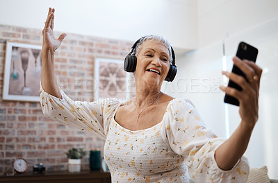 Buy stock photo Shot of a senior woman dancing while using a smartphone and headphones at home