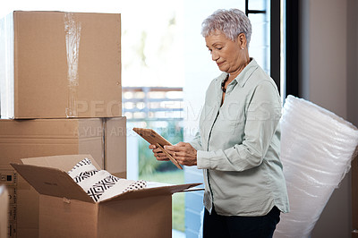 Buy stock photo Shot of a senior woman looking at a photograph while packing boxes on moving day