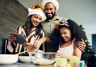Buy stock photo Shot of a happy young family using a digital tablet while preparing a meal during Christmas at home