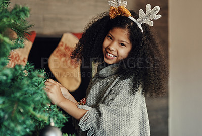 Buy stock photo Portrait of a cute little girl decorating a Christmas tree at home
