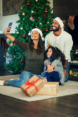 Buy stock photo Shot of a happy young family taking selfies while opening Christmas presents at home