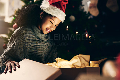 Buy stock photo Shot of a cute little girl opening Christmas presents at home