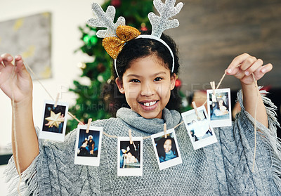 Buy stock photo Shot of a cute little girl hanging up family photographs during Christmas at home