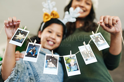 Buy stock photo Shot of a happy young mother and daughter hanging up family photographs during Christmas at home