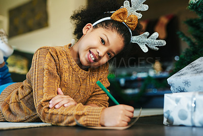 Buy stock photo Shot of a cute little girl writing in a card during Christmas at home