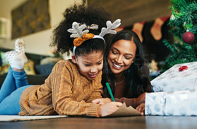 Buy stock photo Shot of a cute little girl writing in a card with her mother during Christmas at home