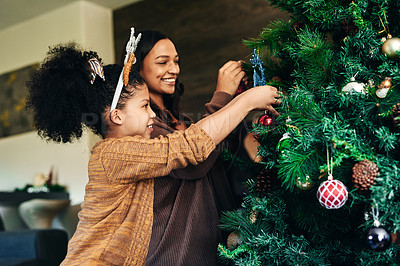 Buy stock photo Shot of a happy young mother and daughter decorating the Christmas tree at home