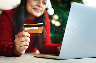Buy stock photo Shot of a happy young woman using a laptop and credit card during Christmas at home